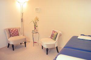 Blick in den Behandlungsraum mit Liege und zwei Sesseln. Der Raum erscheint in einem warmen Licht.