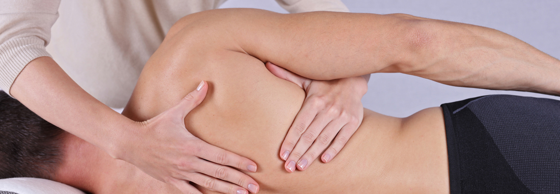 Eine Therapeutin behandelt mit beiden Händen einen Mann am Rücken. Der Oberkörper ist frei.
